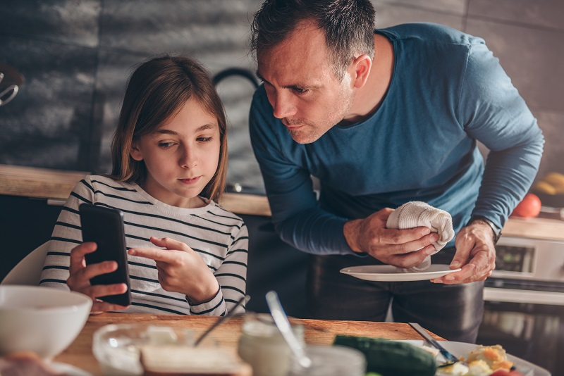 teenage daughter showing something on her mobile phone screen to her Dad - at the kitchen table